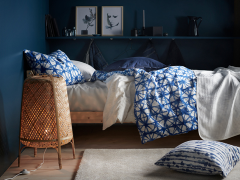 The side of a bed with a blue patterned duvet and a blue pillow, next to a wicker lamp.