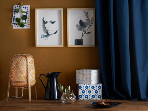 Decorative items next to a blue curtain including a wicker lamp, a black pitcher, colorful boxes and pictures on the wall.