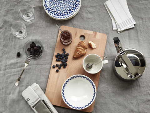 Top down view of a cutting board with blueberries, a croissant, some jam, and blue patterned bowls with a tea kettle nearby.