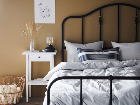 A Black metal framed bed with a white blanket and light pillows, and a white side table next to it.
