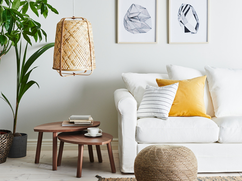 A white sofa next to two nested side tables and a hanging wicker pendant lamp hanging above.