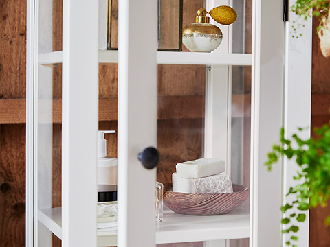 A close-up shows bathroom products in HEMNES high cabinet with glass door and its white-stained solid pine frame and shelves.