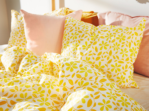 A close-up shows a 100% cotton JUVELBLOMMA quilt cover and pillowcase with a yellow flower and leafy vine pattern on white.