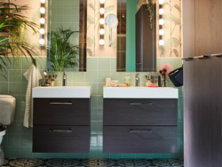 A pink and green bathroom with a black/white patterned floor. Two black-brown wash stands are placed next to each other.