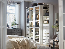 A bedroom with a white wardrobe with glass doors, a dark gray chest of drawers and a gray-beige armchair.