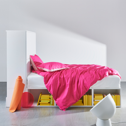 The white PLATSA bed frame with storage showing open shelves underneath the bed and closed storage with doors at one end.