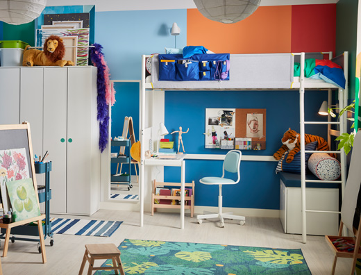 A colourful children's room with a white loft bed, an easel, a leaf-patterned rug and a blue children's desk chair.
