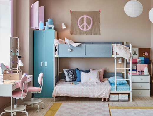 A blue and pink children's room for siblings with a white bunk bed, a white shared desk and light pink desk chairs.