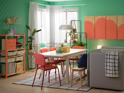 A dining room with a white table، red chairs، and grey sofa and a cabinet and a shelving unit that's painted in coral colour.