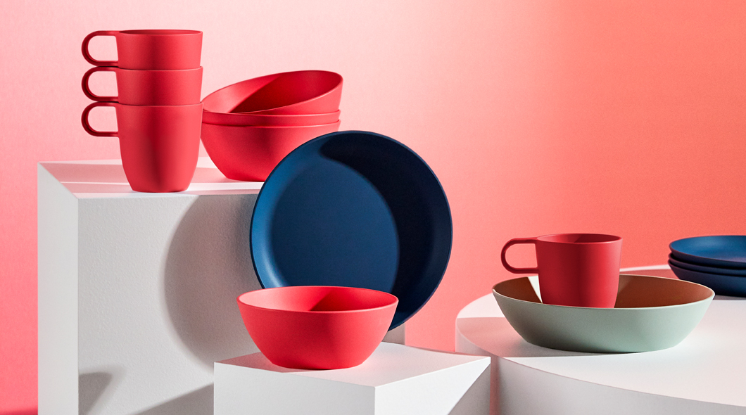 A selection of TALRIKA mugs، bowls and plates in bright red، light green and dark blue.