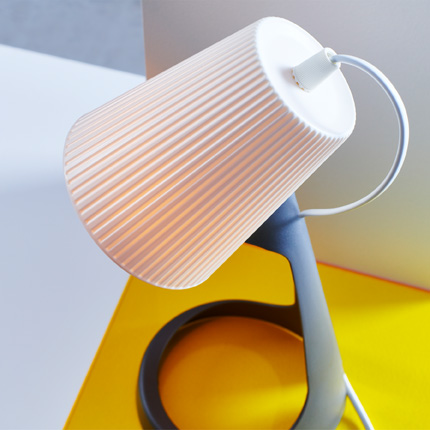 A close-up of SVALLET work lamp showing its targeted lamp shade in white and lamp base in dark grey.