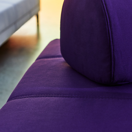 A close-up of a purple FLOTTEBO sofa-bed with stitching details and large movable cushions to place as you wish.