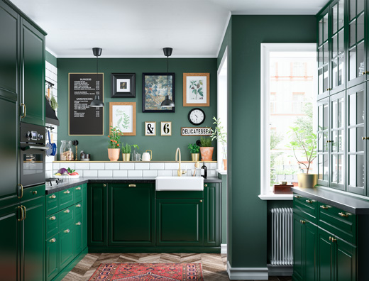 A kitchen in dark green with white tiles, glass doors, brass-coloured mixer tap and a picture wall with a variety of frames.