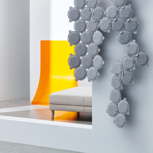 Many circular ODDLAUG sound absorbing panels made of grey felt to absorb annoying sounds.
