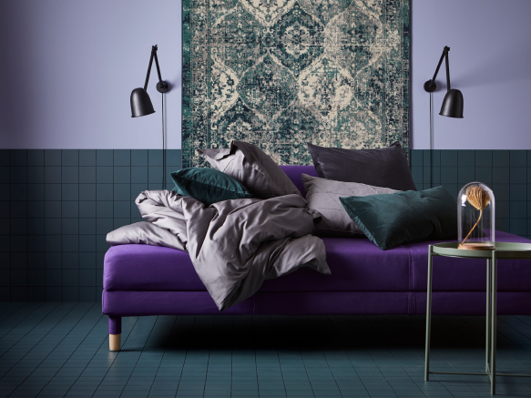 A purple sofa, a quilt cover and pillowcases in dark grey, dark turquoise cushions and green-patterned rug on a wall.
