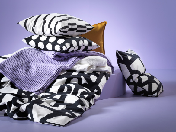 A lilac scene with a black/white patterned quilt cover and pillowcases, a lilac throw and a yellow cushion cover.