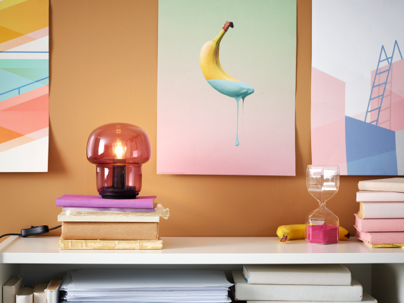A small lit purple table lamp in glass on a pair of books, a banana poster and a decorative hourglass in glass and pink.