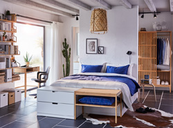 Bedroom with a white bed frame, blue bed textiles and a pendant lamp, a desk, a wardrobe and shelves in warm bamboo.