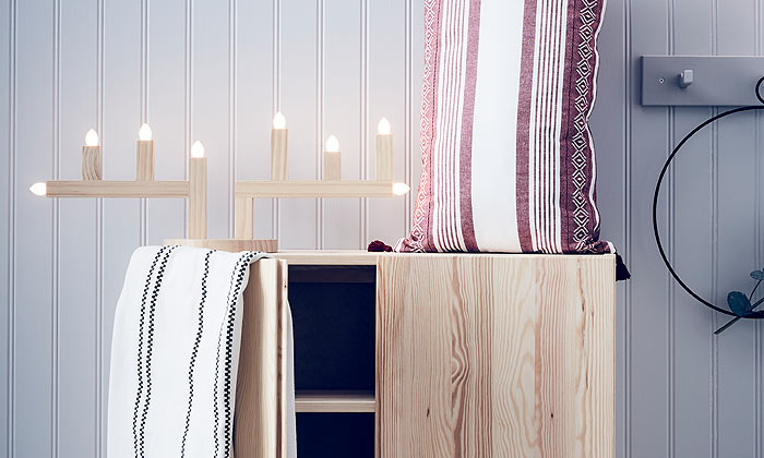 The STRÅLA LED antlers shaped candelabra on a pine cabinet next to VINTERFEST red and white striped pillow case.