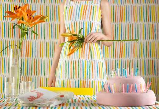 A white metre fabric with stripes in yellow, orange, blue, green and pink.