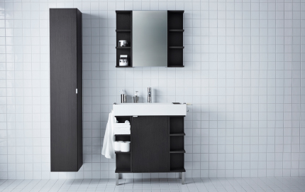A bathroom sink and black cabinet, mirror cabinet and long black cupboard in a white-tiled room.
