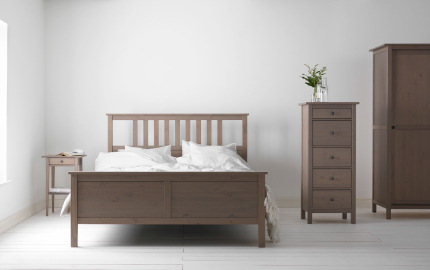 A wooden bed with white bedding and a side table, narrow chest of drawers and a wardrobe in a white room.