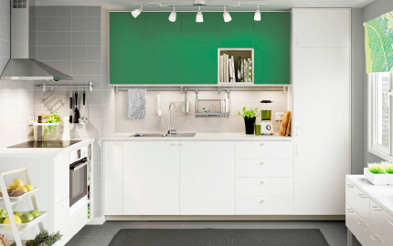 A white kitchen with green accent doors and white worktops. Combined with stainless steel extractor hood and white oven.