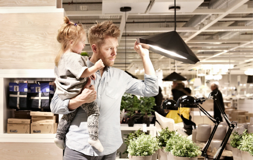 A man holding a little girl looking at a ceiling lamp in an IKEA store.