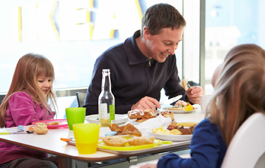 A father and his two young daughters eating a meal at a cafe table with the IKEA sign in the background.
