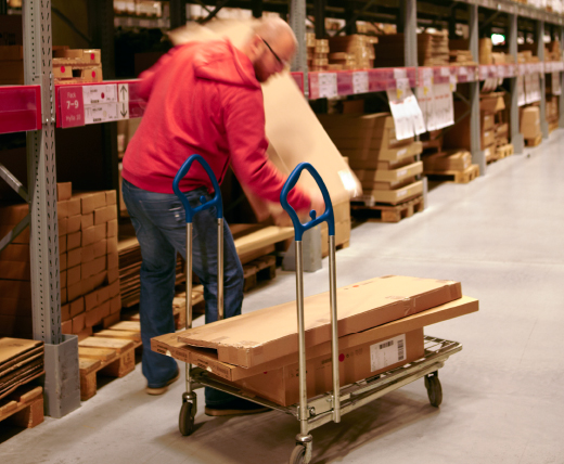 A man loading boxes from a storage warehouse onto a trolley.