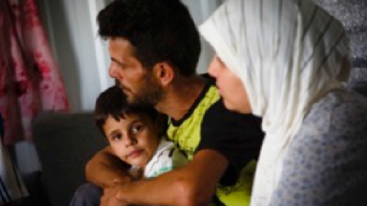 A regugee man holds his young son and as his wife sits beside him in a UNHCR shelter