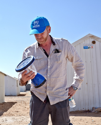 UNHCR staff members looks lovingly at a UNHCR solar lantern, standing with his hand on his hip, a water bottle in his hand, a baseball cap on his head and better shelters in the background
