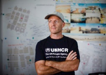 Portrait of Paul Quigley, a UNHCR staff member standing with his arms folded across his chest and a large map of the camp on the wall behind him