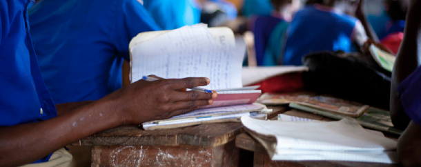 a student in sierra leone sits at a desk looking through a book