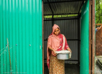 a green tin shack with a woman standing in the doorway holding a pot of food