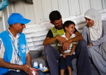 UNHCR Field Associate Khaled Al-Jaman laughs with four-year-old Mutaz in the family shelter at Azraq refugee camp.