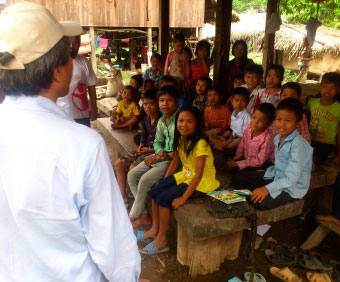 Man in white shirt and off-white cap facing a group of children.