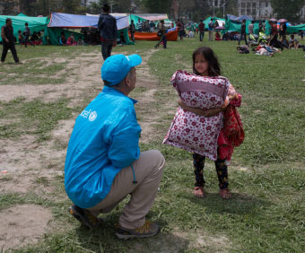 UNICEF coworker kneeling across from a girl holding a pillow.