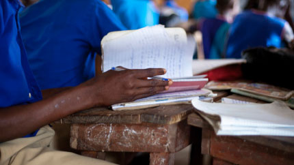 Close up a child in a blue t-shirt holding a notebook.