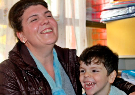 Female smiling and holding a laughing boy.