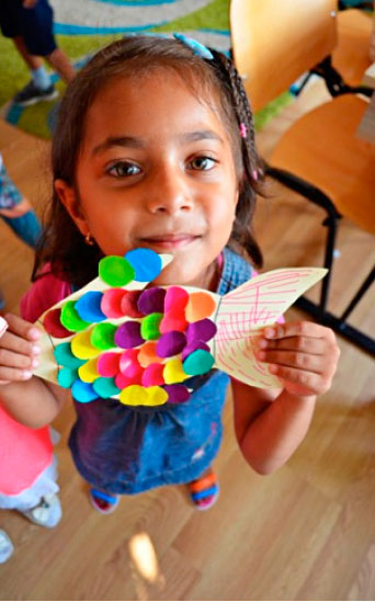 A girl holding a paper drawing in the shape of a fish.