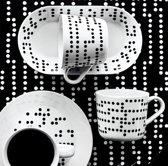 A table, seen from above, set with white plates and mugs featuring irregular black dot patterns.