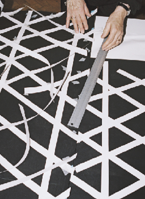 Close-up of a woman making a white geometric pattern on a black fabric.