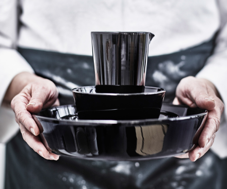 A person holding a jug and two bowls in black glass