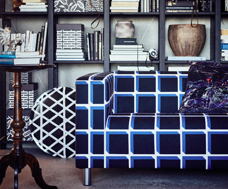 A two-seat sofa with a cotton cover in a black and blue geometric pattern and behind the sofa a black shelving unit filled with boxes and books.