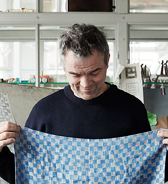 Dutch designer Piet Hein Eek proudly holds the chequered blue tea towel he designed for the INDUSTRIELL collection.
