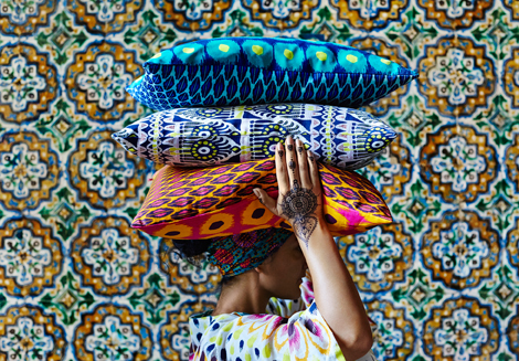 A woman with henna tattoos on her hands, carrying colourful cushions with batik inspired patterns, on her head.