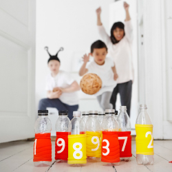 Children bowling with empty bottles covered with numbered elastic bands in red and yellow.