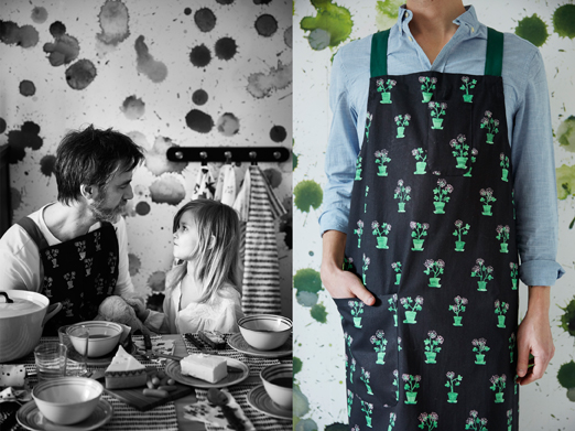 A man wearing a black apron with green floral pattern.
