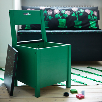 A green chair with storage under the seat.